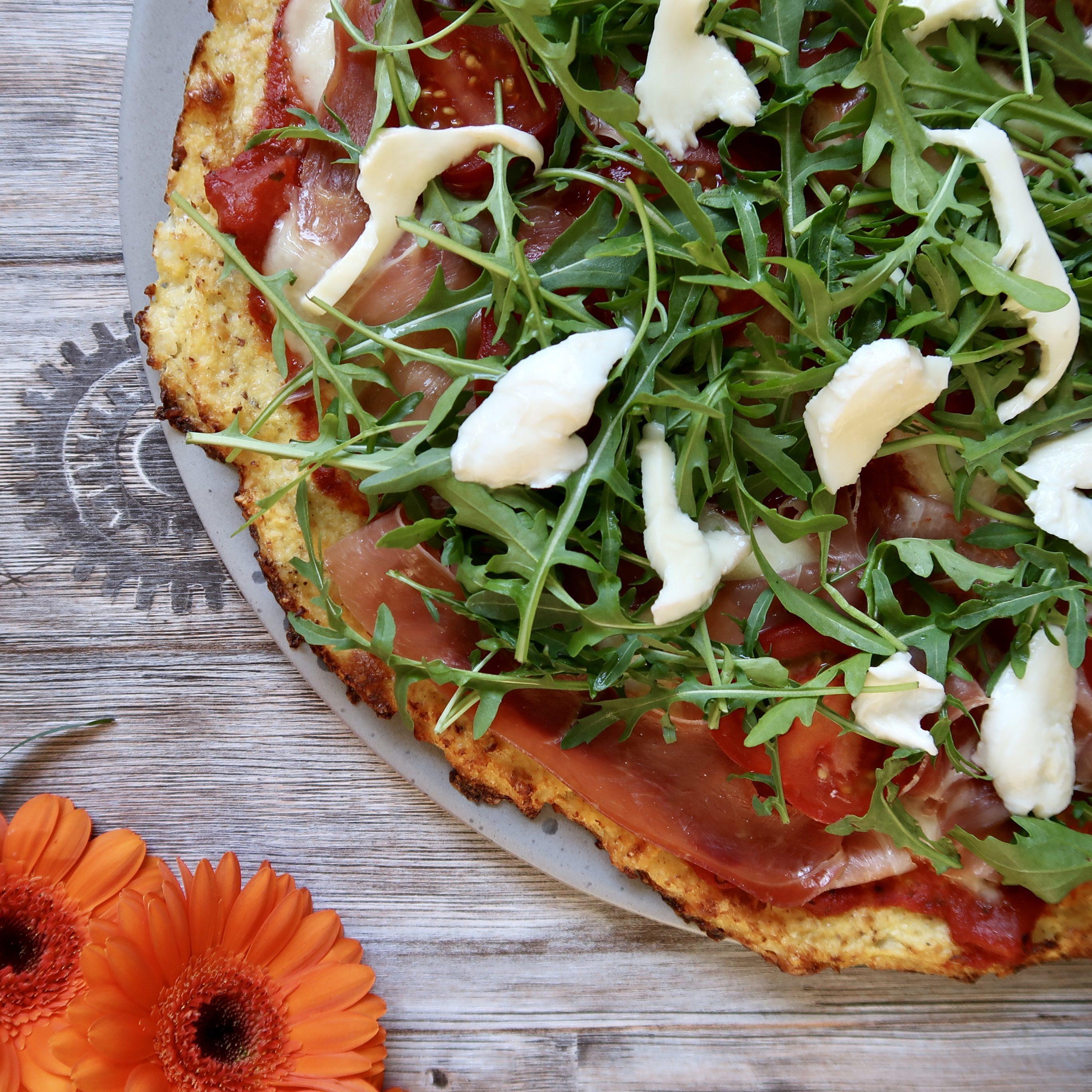 Blomkålspizzamed seranoskinke, mozzarella, tomater og rucolasalat